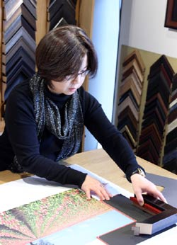 Owner Hong Zhu designs framing for a print